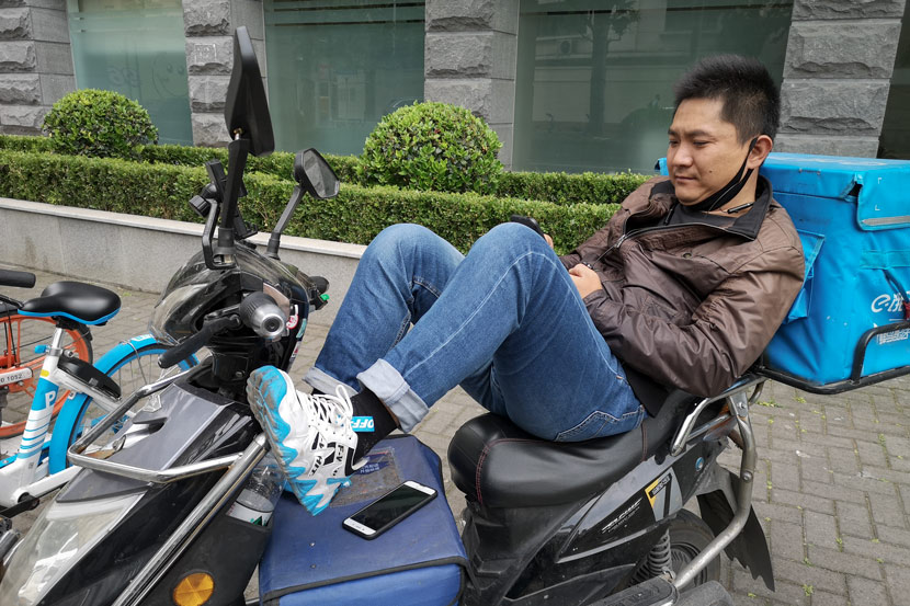 A delivery driver surnamed Jia looks at his phone during his downtime, Shanghai, May 14, 2020, Kenrick Davis/Sixth Tone