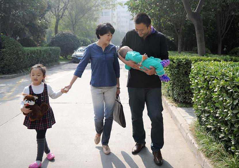 A family walk in a residential area in Xi'an, Shaanxi province, Oct. 26, 2014. People Visual