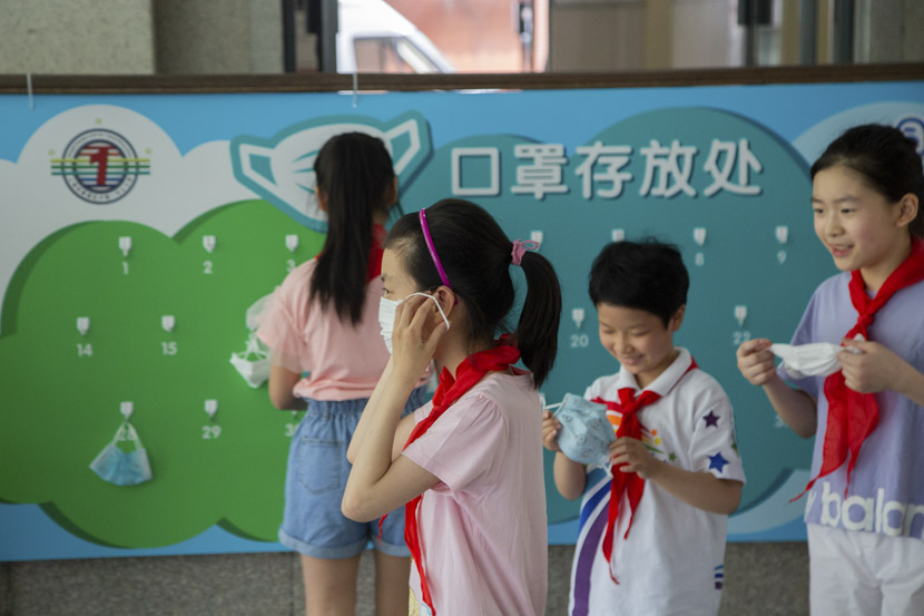 Ahead of PE class, students hang their face masks on numbered hooks at Luwan No. 1 Central Primary School in Shanghai, May 18, 2020. Primary school students were some of the last in the country to restart class after the COVID-19 pandemic. Shi Yangkun/Sixth Tone