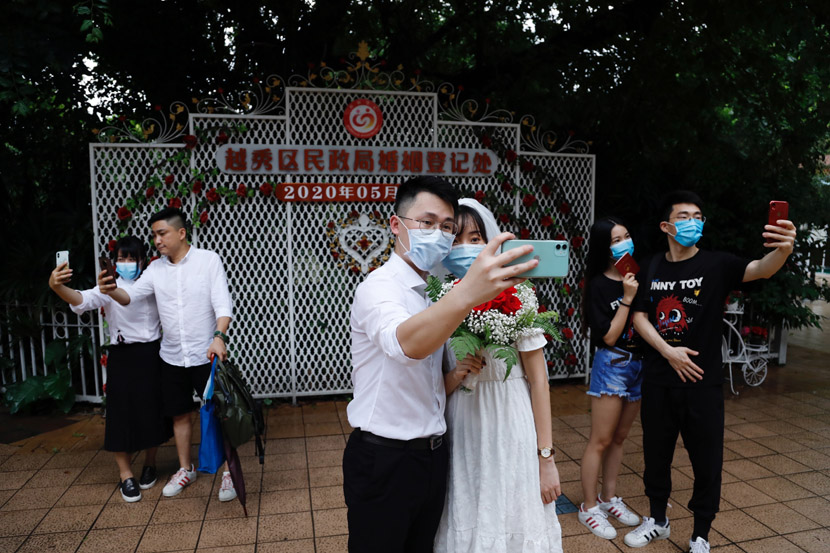 """Couples pose for selfies outside the marriage registration office in Yuexiu District, Guangzhou, Guangdong province, May 20, 2020. The date, which is pronounced similar to """"I love you"""" in Chinese, is seen as an auspicious one for getting married, especially by young Chinese. Chen Hui/Southern Metropolis Daily/People Visual"""
