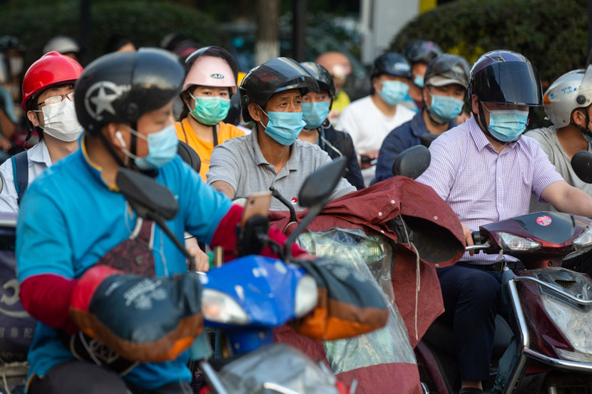 """Riders don headgear in Hangzhou, Zhejiang province, May 18, 2020. In an effort to boost road safety, China unveiled a """"One Belt, One Helmet"""" policy earlier this month, though officials were forced to partially delay implementation after helmet prices skyrocketed nationwide. Chen Zhongqiu/People Visual"""