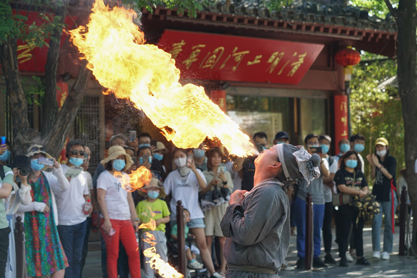 A folk performer spits fire at Millennium City Park in Kaifeng, Henan province, May 22, 2020. Ma Jian/People Visual
