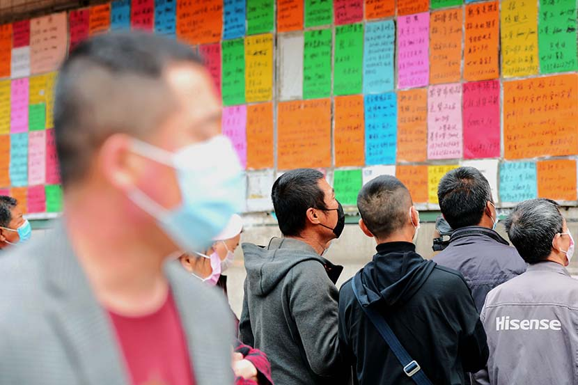 Jobseekers check job ads posted at an employment fair in Qingdao, Shandong province, April 8, 2020. People Visual