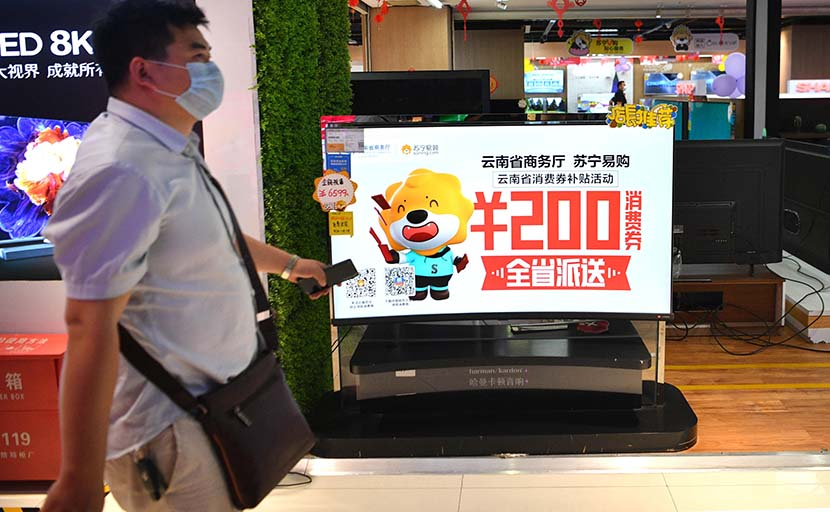A poster promoting consumption coupons released by provincial authorities is displayed at a shopping mall in Kunming, Yunnan province, April 11, 2020. Liu Ranyang/CNS/People Visual