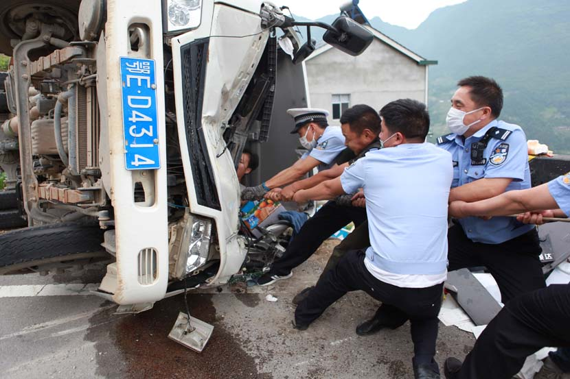 Police officers help rescue a man from the smashed cab of a truck after a traffic accident in Yichang, Hubei province, May 28, 2020. Wu Lingjian/People Visual