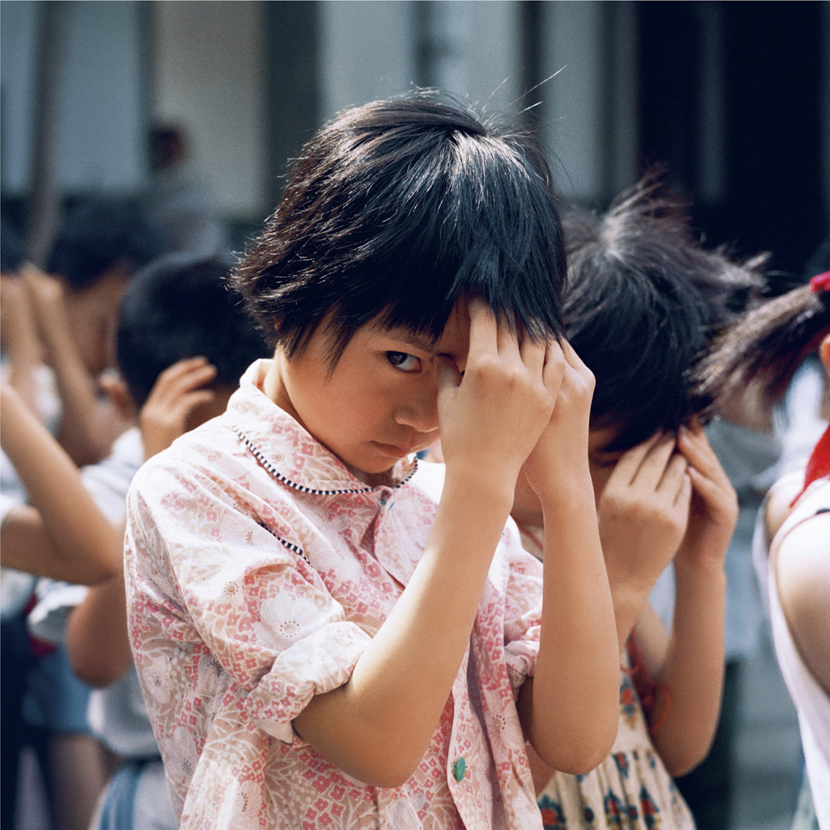 "A girl steals a glance during ""eye exercises,"" massages for releasing eye strain, in Chengdu, Sichuan province, 1981-1982. Courtesy of Ryoji Akiyama via Seisodo"