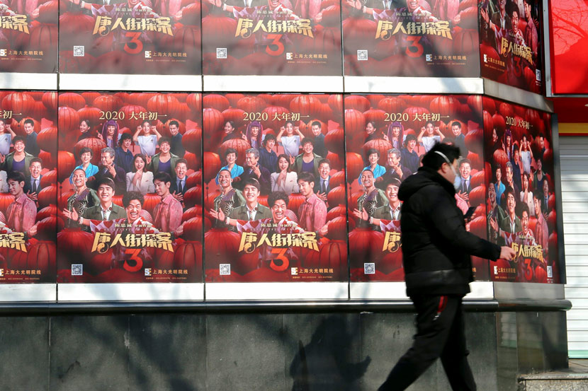 A man walks past a wall plastered with film posters outside a movie theater in Shanghai, Feb. 24, 2020. Chen Yuyu/People Visual