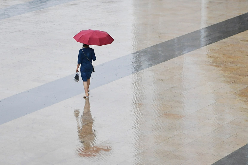 A woman walks through a square during a rainy day in Shanghai, June 3, 2020. Zhou Junxiang/IC