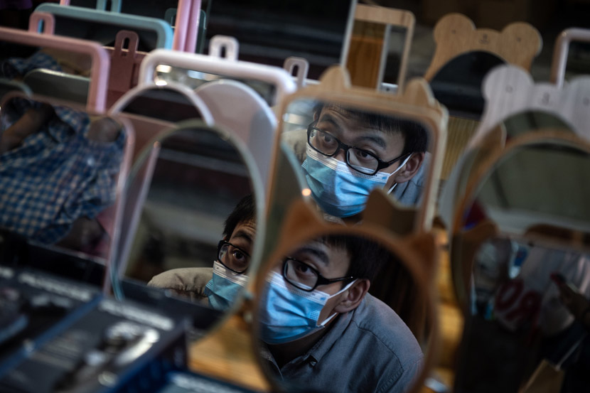 A shopper checks his reflection at a night market in Wuhan, Hubei province, June 3, 2020. Don McCurren/IC