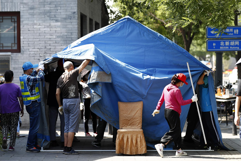 People dismantle a tent used for checking entrants' body temperatures and registering vistors during the pandemic at a residential community in Beijing, as the capital lowered its public health emergency response level, June 6, 2020. Fu Tian/CNS/People Visual