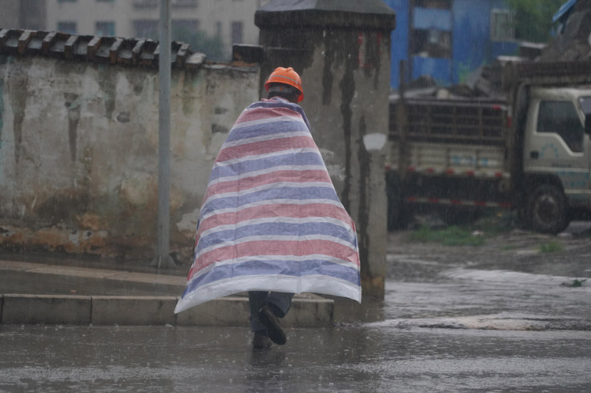 A migrant worker wraps himself in a plastic sheet on a rainy day in Kunming, Yunnan province, June 18, 2020. Liu Ranyang/CNS/People Visual