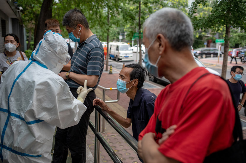 A nurse explains the appointment system to patients outside a fever clinic in Beijing Puren Hospital in Beijing, June 17, 2020. Li Junhui/China Youth Daily/People Visual