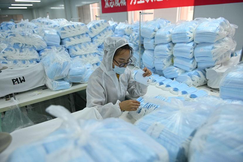 A worker sorts face masks at a factory in Shenyang, Liaoning province, May 16, 2020. Yu Haiyang/CNS/People Visual