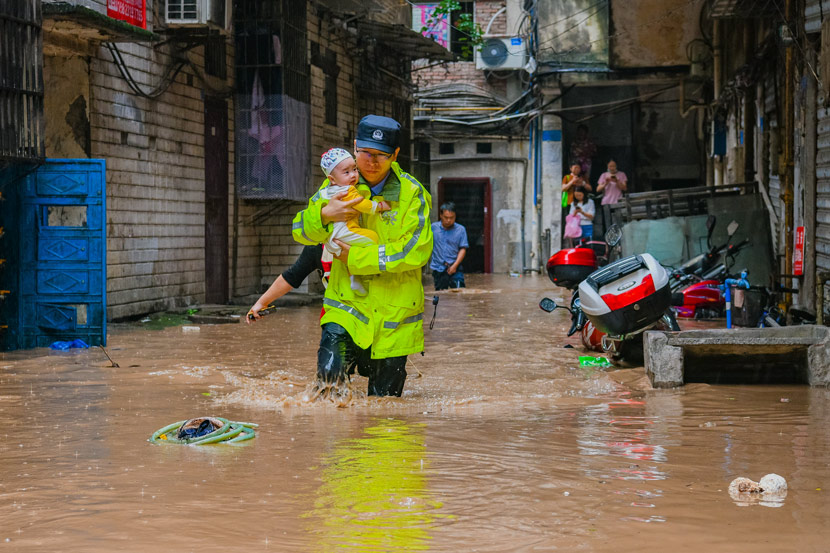 A police officer rescues a baby from a flooded neighborhood in Qijiang District, Chongqing, June 22, 2020. Chen Xingyu/People Visual