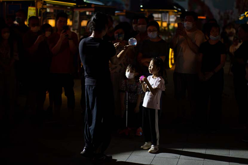 A child takes part in a performance at Yu Garden in Shanghai, June 23, 2020. With the tourism industry still feeling the effects of the coronavirus pandemic, Yu Garden launched a series of interactive attractions to lure visitors ahead of the Dragon Boat Festival. Shi Yangkun/Sixth Tone