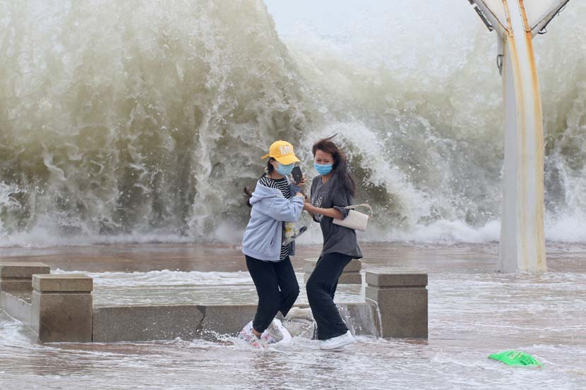Two women run away from a large wave in Yantai, Shandong province, June 24, 2020. The city has been battered by storm surges this week. People Visual