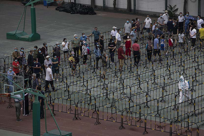 People wait to be tested at a coronavirus nucleic acid testing site in Chaoyang District, Beijing, June 23, 2020. Jiang Qiming/CNS/People Visual