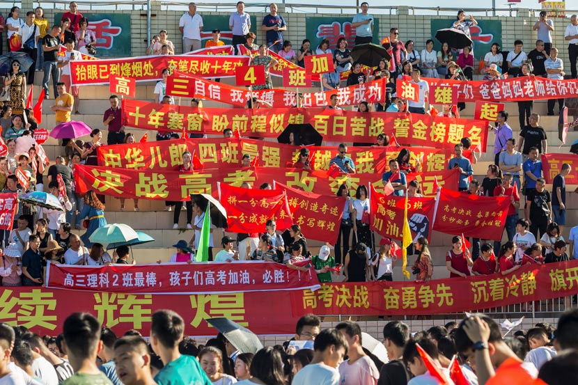 "Parents of students who will soon take the ""gaokao"" hold banners with supportive messages at a high school in Mianyang, Sichuan province, June 5, 2019. Zhang Cheng'an/People Visual"