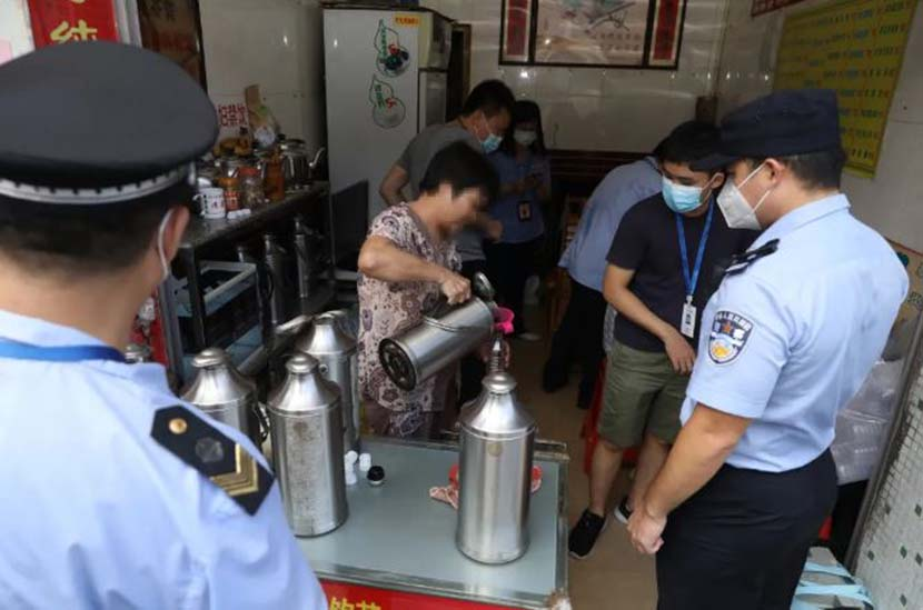"""Police officers investigate a tea shop that was found to be adding unapproved pharmaceutical ingredients to its """"cooling tea"""" product in Guangzhou, Guangdong province, 2020. From the Guangzhou police's public WeChat account"""