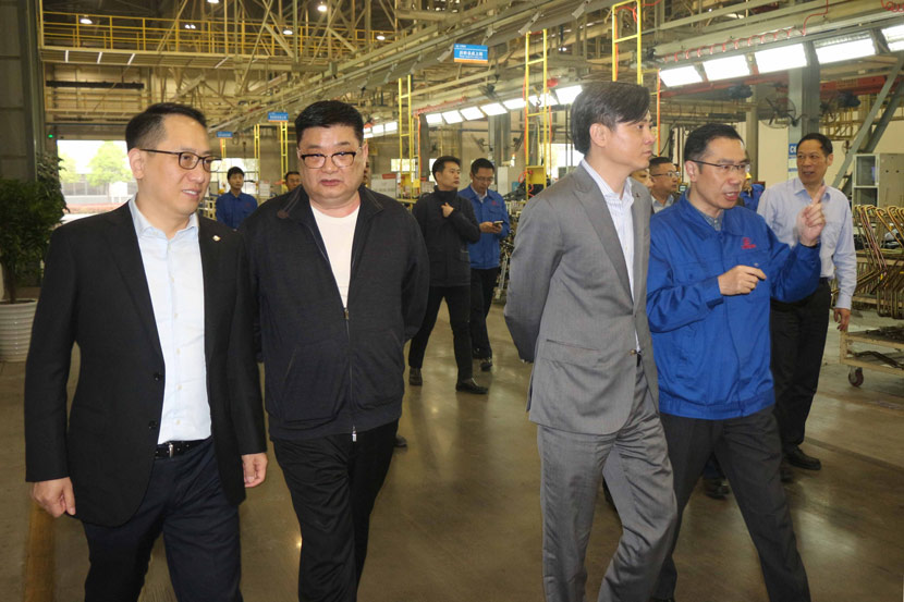 Jia Zhihong (second from left) and Zhang Bo (third from left), chairman of Minsheng Trust, visit a factory in Shiyan, Hubei province, April 12, 2019. From Kingold Group's website