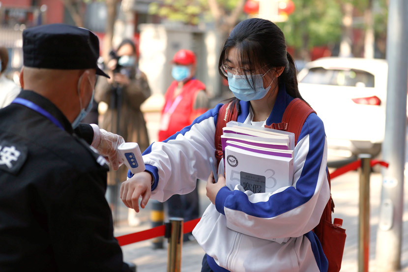 A security guard checks the body temperature of a student at the entrance to a high school in Beijing, April 27, 2020. It was the first day senior high school students returned to school following the COVID-19 outbreak. Fu Tian/CNS/People Visual