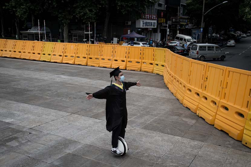 A college graduate in a cap and gown wheels around Wuhan University, Hubei province, June 11, 2020. University seniors in Wuhan graduated immediately after they returned to schools. IC