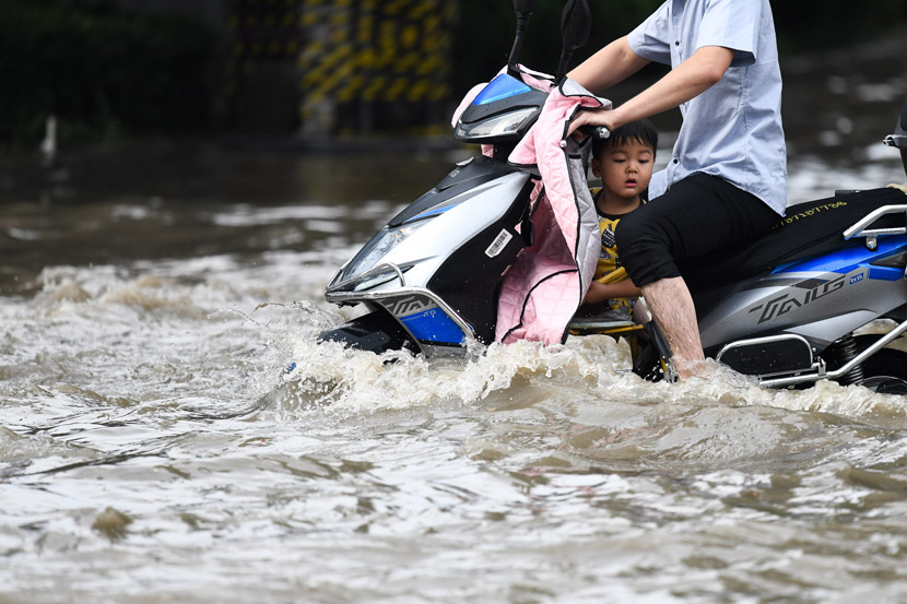 A man and child make their way down a flooded street in Zhengzhou, Henan province, July 4, 2020. IC