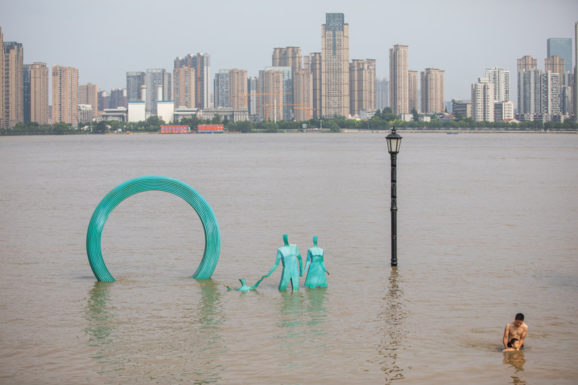 A father and son swim by the riverside in Wuhan, Hubei province, July 3, 2020. The flood-prone city was inundated again this week. People Visual