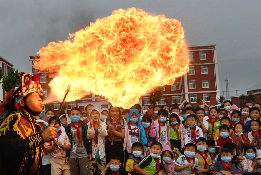 A man spits fire in a Sichuan Opera performance during the Cultural and Natural Heritage Day, at a school in Zaozhuang, Shandong province, June 12, 2020 Liongxian/People Visual