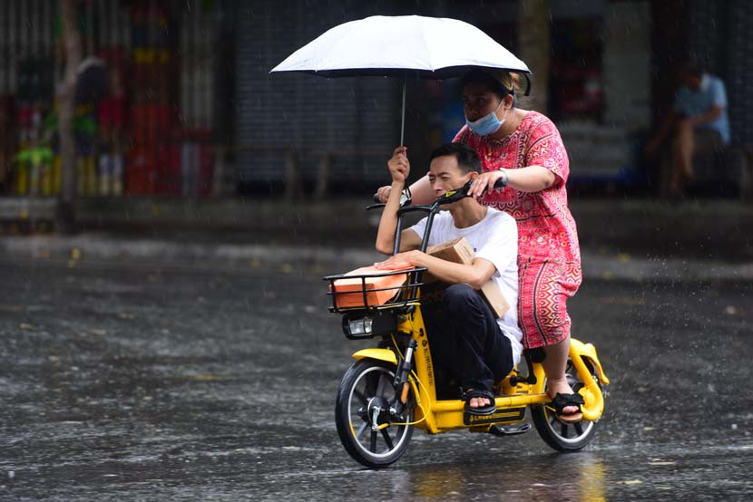 A man and a woman ride on an electric bike in the rain, Qionghai, Hainan province, June 14, 2020. People Visual