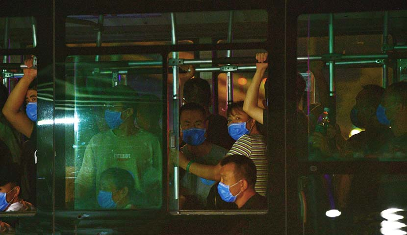 Workers at the Xinfadi market are evacuated by bus in Beijing, June 13, 2020. On that day, officials reported that 46 people connected to the Xinfadi market — the largest farmers market in China's capital — had tested positive for the coronavirus. Fu Ding/Beijing Youth Daily/People Visual