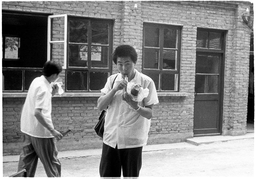Students grab a snack outside the exam venue, Beijing, 1979. Ren Shulin for Sixth Tone