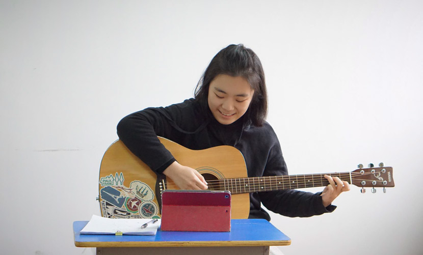 Lin Qingyue, a sophomore and member of SMC's music therapy team, plays guitar during an online therapy session, 2020. Courtesy of Yang Yanyi
