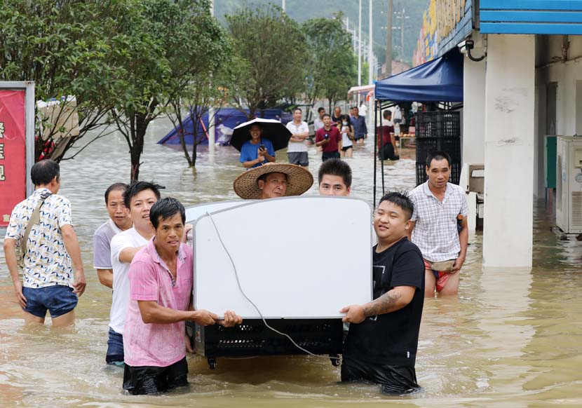 People move electronic appliances out of a flooded area in Liuzhou, Guangxi Zhuang Autonomous Region, July 11, 2020. People Visual