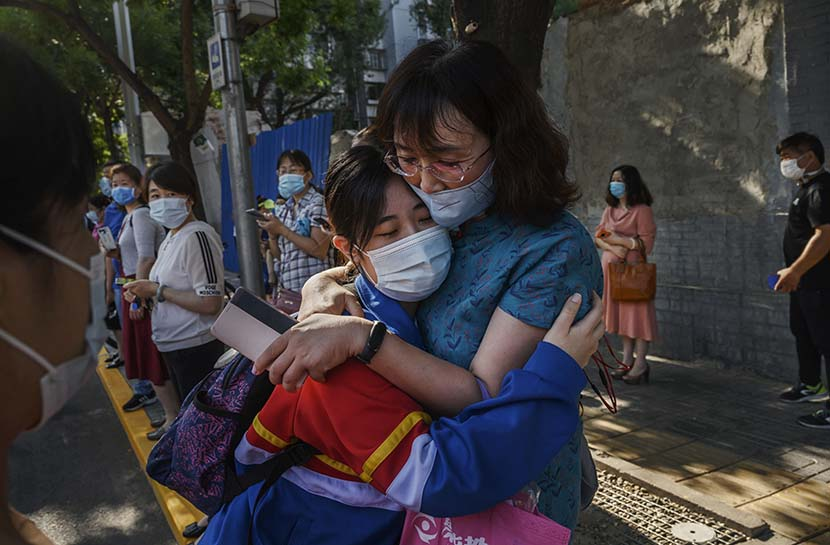 A mother and a daughter hug each other before the gaokao college-entrance exam starts at a high school in Beijing, July 7, 2020. People Visual