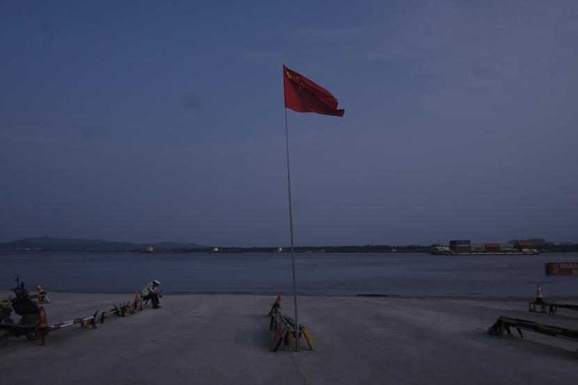 A police officer sits near a river with unusually high water levels in Jiujiang, Jiangxi province, July 14, 2020. Wu Huiyuan/Sixth Tone