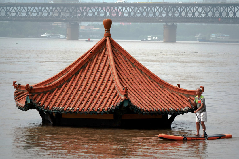 A man on a raft paddles by a submerged building on a branch of the Yangtze River in Wuhan, Hubei province, July 9, 2020. People Visual