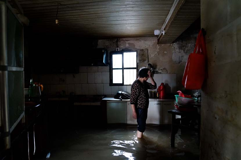 A woman stands in her flooded kitchen, Lu'an, Anhui province, July 22, 2020. People Visual