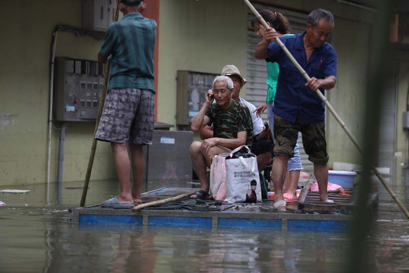 A man calls family members to tell them he's safe as rescuers transfer him from a flooded area in Chaohu, Anhui province, July 23, 2020. People Visual