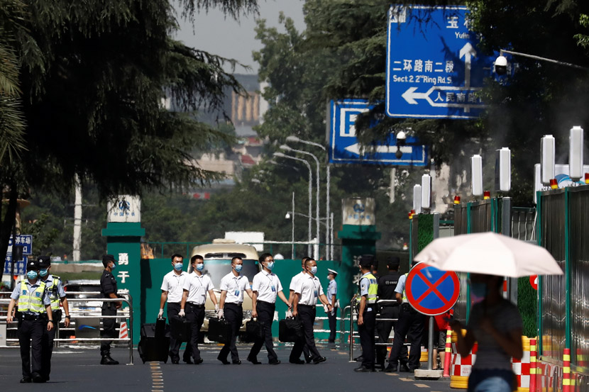 Security personnel walk in front of the now-closed U.S. Consulate in Chengdu, Sichuan province, July 27, 2020. Thomas Peter/People Visual