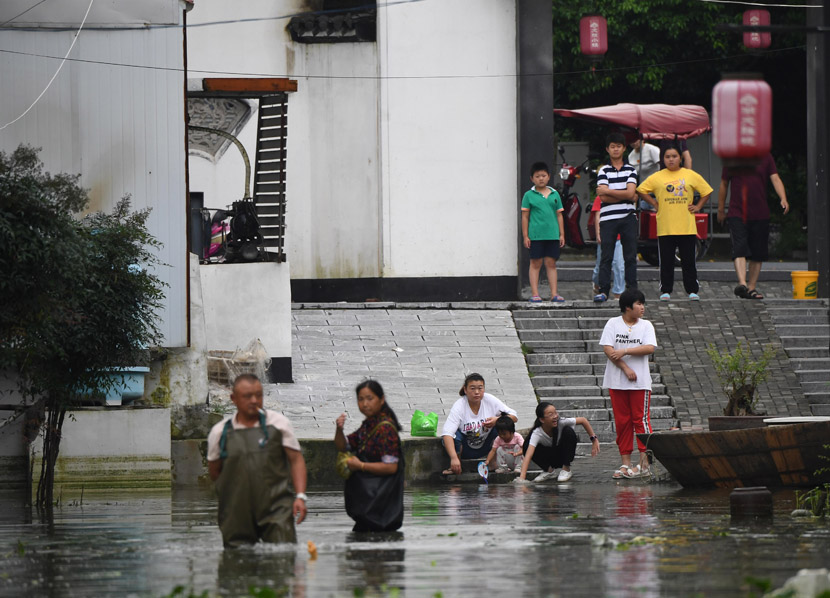 People wade through floodwaters in the town of Zhongmiao, Anhui province, July 28, 2020. Cui Nan/CNS/People Visual