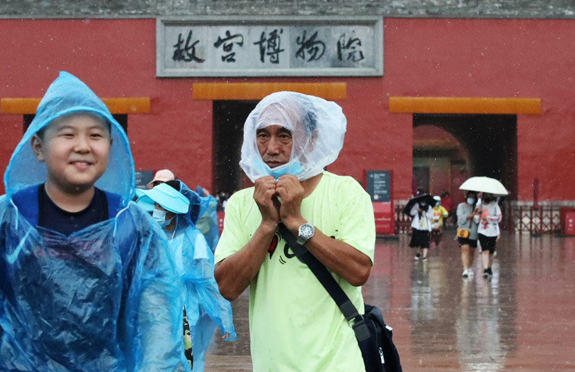 Tourists visit the Palace Museum on a rainy day in Beijing, July 31, 2020. IC