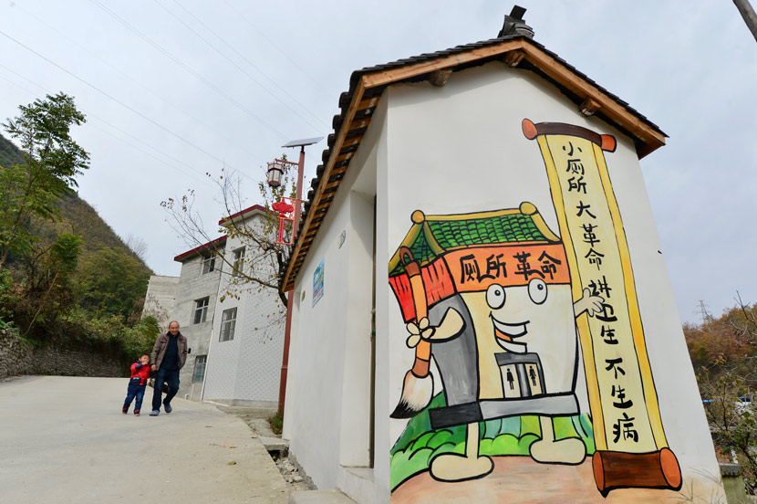 A wall painting promoting the 'toilet revolution' in Xiaogou Village, Xiangyang, Hubei province, Nov. 22, 2018. The slogan reads: 'Small toilet, big revolution; Pay attention to hygiene and you won't get sick!' Yang Tao/People Visual