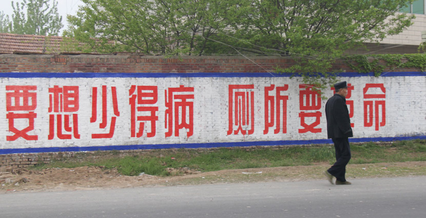 "A villager walks past a slogan, reading, ""If you want to get sick less, then we need a toilet revolution,"" in Yucheng County, Henan province, April 23, 2010. IC"