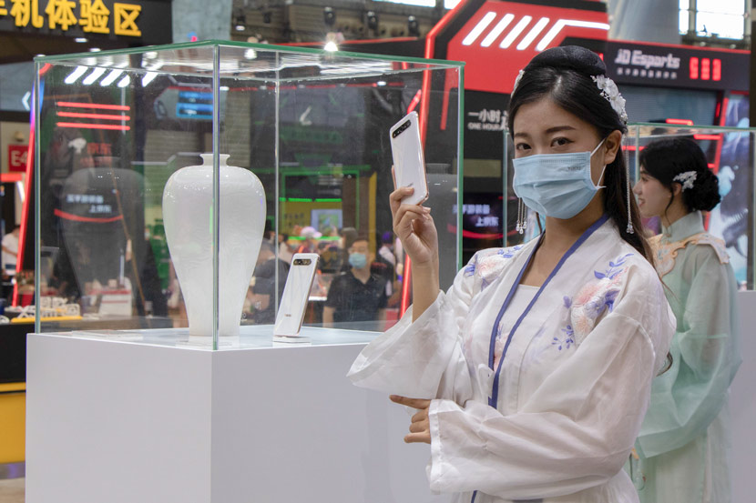 "A woman in traditional ""hanfu"" clothing promotes a new smartphone during the ChinaJoy digital entertainment expo in Shanghai, July 31, 2020. Kenrick Davis/Sixth Tone"