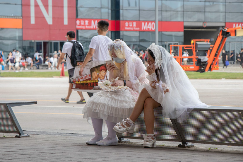 People in wedding dresses sit outside the conference venue for the ChinaJoy digital entertainment expo in Shanghai, July 31, 2020. Kenrick Davis/Sixth Tone