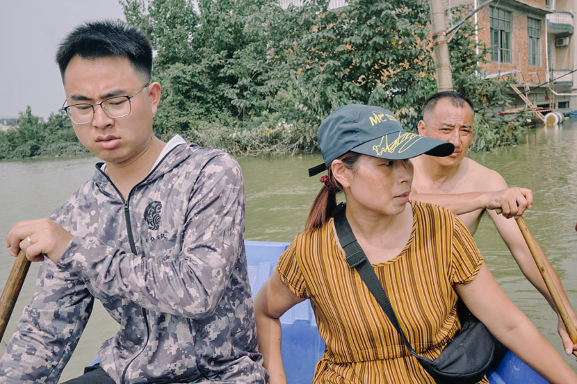 Wu Youfeng (center) and her family paddle toward their home in Youdunjie Town, Poyang County, Jiangxi province, July 15, 2020. The family own a grocery store and suffered around 1 million yuan worth of losses during the flood. Wu Huiyuan/Sixth Tone