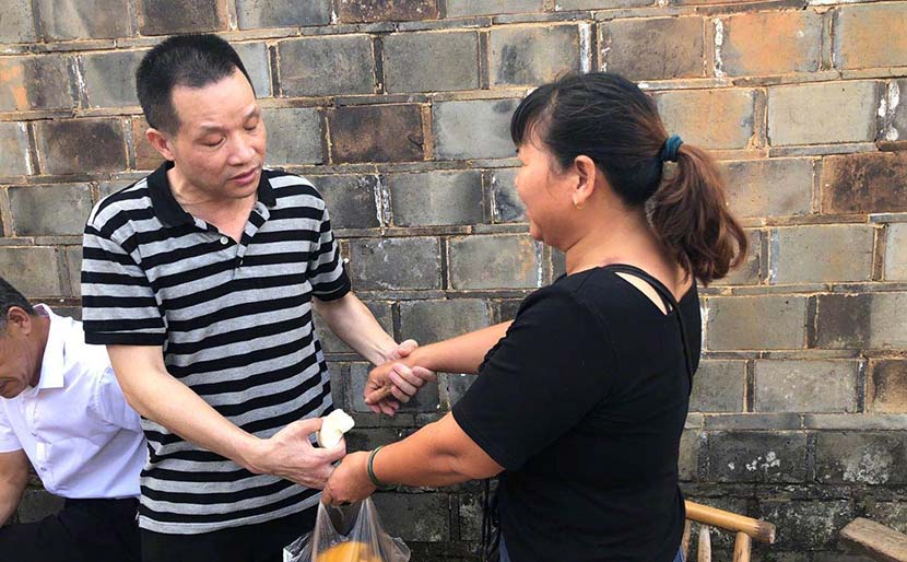 Zhang Yuhuan holds his ex-wife's hands after his acquittal for murder and release from prison, Zhangjia Village, Jinxian County, Jiangxi province, Aug. 4, 2020. From The Paper