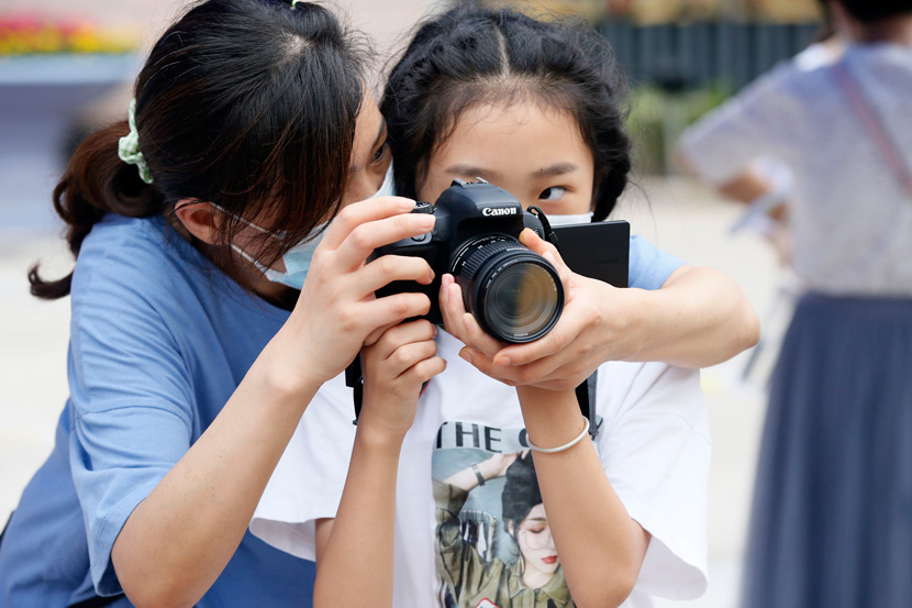 A mother teaches her daughter how to capture the scene outside of an exam site during this year's High School Entrance Exam in Xi'an, Shaanxi province, July 18, 2020. Chen Tuanjie/Chinese Business View/People Visual
