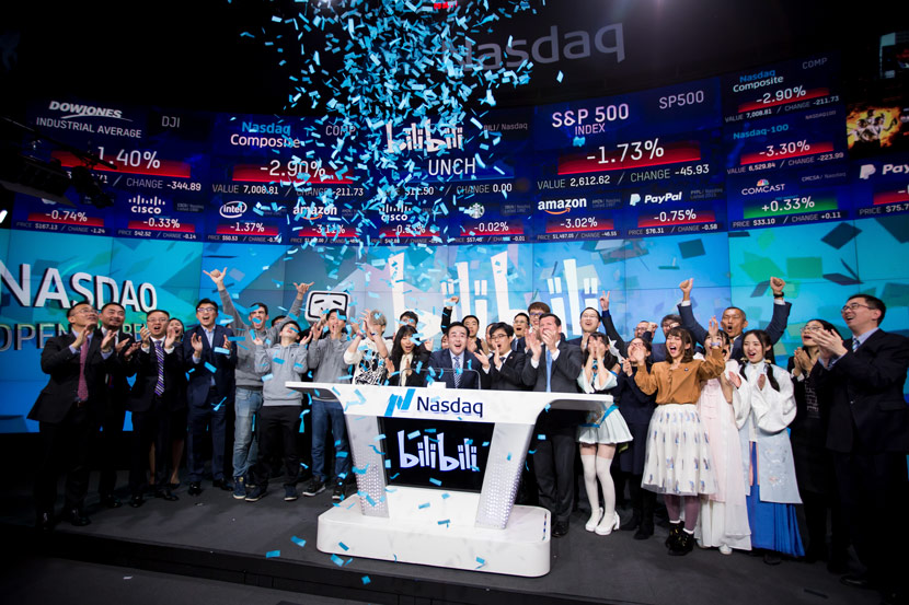 Rui Chen (center), chairman and CEO of Bilibili Inc., launches the company's initial public offering at the Nasdaq Market Site in New York, March 28, 2018. Michael Nagle/Bloomberg/People Visual